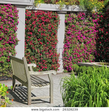 A wooden bench in a colorful garden niche with walls of vibrant flowering impatiens.