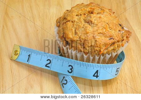 A carrot raisin muffin with a blue measuring tape on a wooden background in a diet / healthy living concept image.