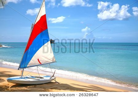 A small sailboat sitting in the shade of an Antigua beach with Hawksbill rock in the background.