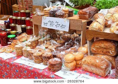 Baked goods and homemade preserves and jams at a farmer's market.
