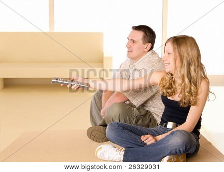 Young Girl and man watching TV together. Girl is holding a remote controller.