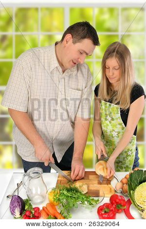 Couple in the kitchen preparing food.