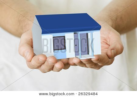 Man's hands holding a house.
