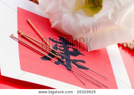 Needles for acupuncturist shown on Chinese health sign.