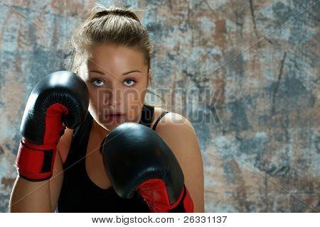 Caucasiana jovem usando luvas de boxe e jogando soco.