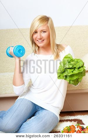 Beautiful woman laughing with head of lettuce and dumb-bell, healthy food concept