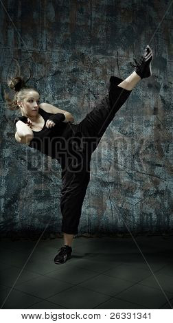 Portrait of young woman practice martial arts - high kick