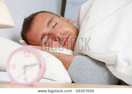 Slapen man. Zijn hand met kussen op de beltoon klok ochtend tonen.