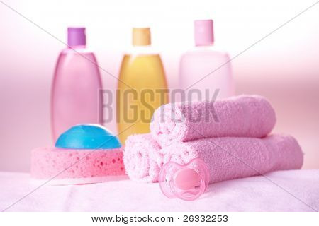 Baby care objects. Olive, shampoo in background towels, sponge, soap and dummy