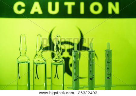 Biohazard sign and ampules with syringes