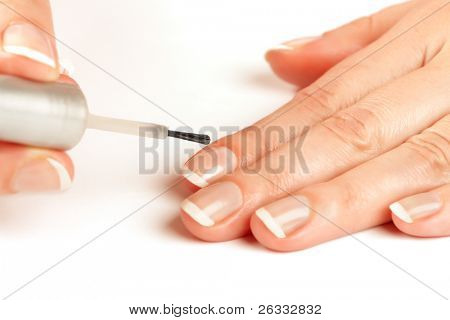 Manicurist applying natural looking nail polish on female fingers in the process of french manicure
