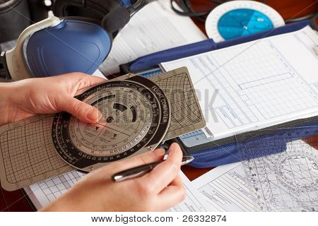 Pilot equipment with airplane pilot hand using flight computer for navigation calculations, other tools like protractor, kneepad with charts and professional headset