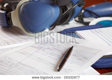 Airplane pilot equipment like flight plan, kneepad with charts and professional headset