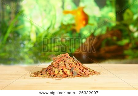 Heap of dry complete multi-ingredient flake food for daily feeding of all ornamental fish with blurred aquarium in the background.
