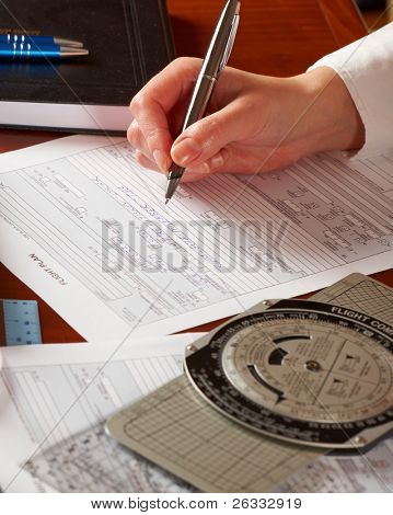 Pilot equipment with airplane pilot hand filling in flight plan, other tools like flight computer used for aviation calculations, protractor and logbook