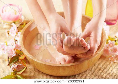 Close-up de belos pés femininos na tigela de madeira cheio de fluido cosméticos, flores ao redor. Co