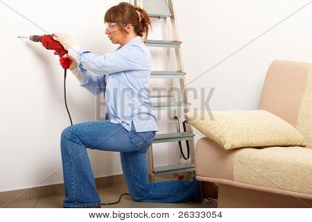 Beautiful woman working drilling hole in white wall in home, wearing protective  gloves and glasses, ladder in background