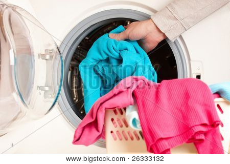 Close-up on female hand putting colorful clothes into washing machine drum