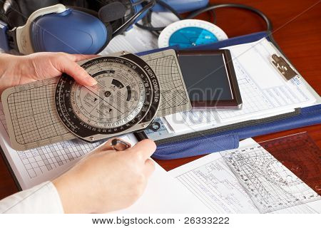Pilot equipment with airplane pilot hand filling in flight plan, other tools like flight computer used for aviation calculations, protractor, kneepad with charts and professional headset