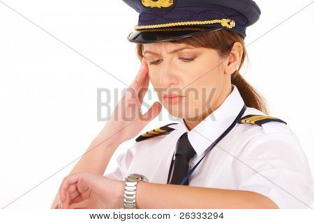 Beautiful woman pilot wearing uniform with epaulets and hat with golden wings, looking at watch and worrying about time, standing isolated on white background.