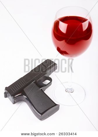 Closeup of pistol and glass of red wine isolated over white background