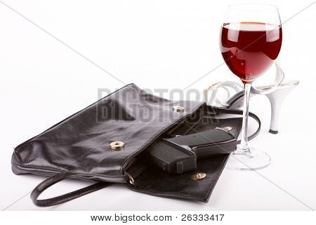 Closeup of woman's bag wit pistol, glass of red wine and isolated and high heel boot over white background