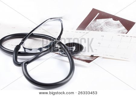 A stethoscope on the top of the EKG chart and USG picture over white background