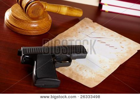 Judges wooden gavel with gun and very old paper with word law in the background - horizontal