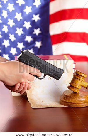Hand with gun aiming at judges wooden gavel with gun and very old paper with US flag in the background - Vertical
