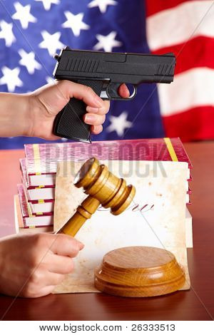 Hand with gun aiming at something, judges wooden gavel and very old paper with US flag in the background