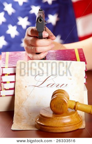 Hand with gun aiming at judges wooden gavel with gun and very old paper with US flag in the background