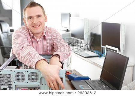 Repairman with computer. Monitors and other laptops in the background waiting for service.