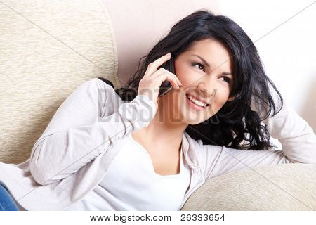 Beautiful young woman talking on the phone laying on the sofa