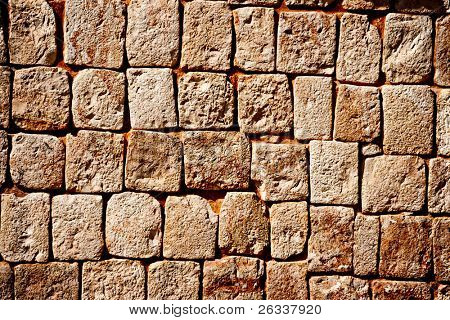 Texture of stone wall of ancient Mayan pyramids in Uxmal, Mexico