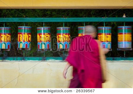 Buddhist monk (llama) rotating prayer wheels on kora