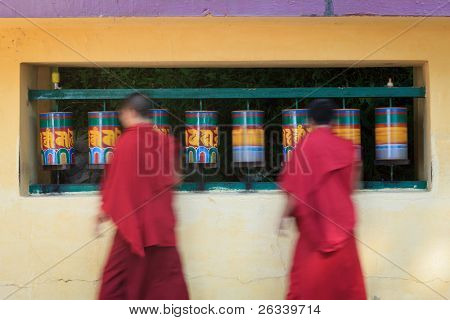 Buddhist monks (llama) passing and rotating prayer wheels on kora around Tsuglagkhang complex in McLeod Ganj, Himachal Pradesh, India