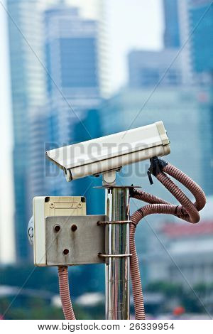 CCTV surveillance camera in Singapore with skyscapers in background