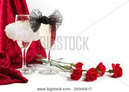 two glasses of champagne with white and black bow knots, carnations and red velvet on white background. Copy space in the top-right corner.