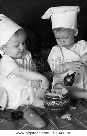 two little boys in the cook costumes at the kitchen sitting on the table. Black and white photo