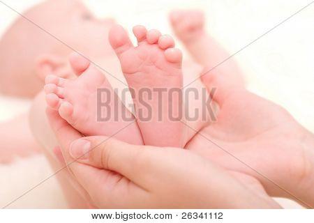 little feet of newborn baby in mother's hands