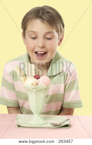 Child Looking At An Ice Cream Sundae On A Table.