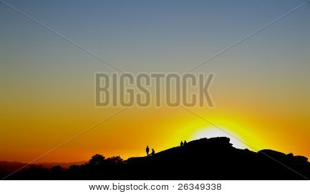 Four men sit on a rock and look after sunset