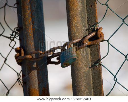 The iron lock on old, rusty doors