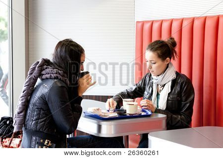 Two girls drink coffee in cafe in the winter