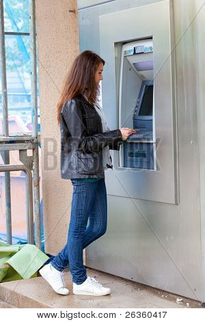 The girl draws out money in a cash ATM