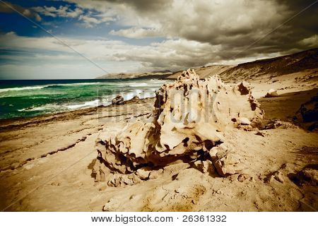 Thunderclouds over the sea and a stone on a beach