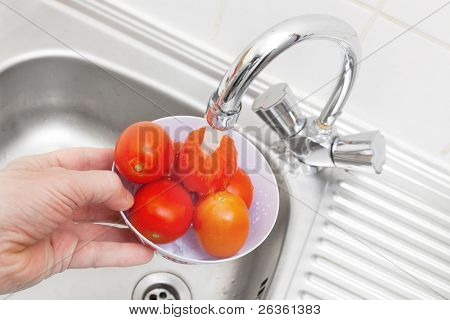 Red tomatoes wash under a water stream