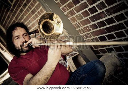 A trombone player plays his trombone in city scene