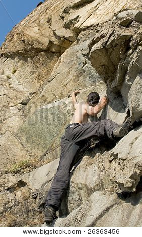 rock climber in action, reaching for the blue