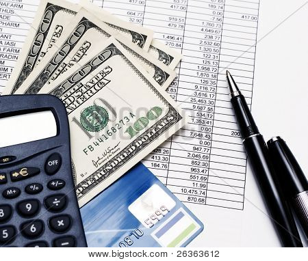 financial statement, calculator, banknotes and pen on top of financial documents